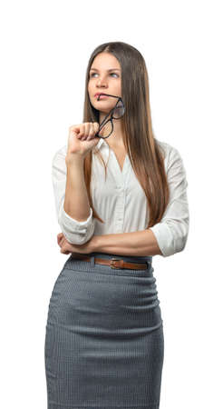 dress code: Cutout businesswoman stands with folded arms looking up. Thinking process. The emergence of new ideas. Success and development. Business staff. Office clothes. Dress code. Presentable appearance. Successful lifestyle.