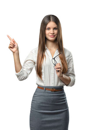 cognition: Businesswoman stands pointing somewhere. Cut-out photo. Learning and cognition. Success and development. Business staff. Office clothes. Dress code. Presentable appearance. Sign and symbol.