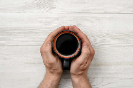 improving: Close-up hands of man holding a cup of coffee. Top view. Workplace of office man. Coffee house. Uplifting mood. Coffee break. Relax. Willingness to work overtime. Conducive working environment. Increasing productivity in the mornings. Improving mood and p