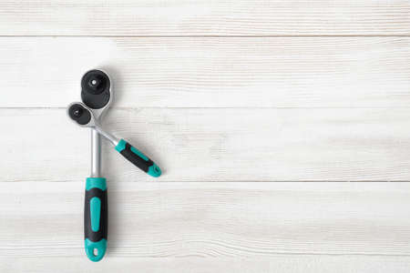 confined: Different-sized ratchet wrenches on wooden background with copy space. Tool for work in confined spaces with nuts, bolts, studs and other fasteners. Ratchet handle. Construction and maintenance. Tool and instrument. Top view composition. Close-up photo. K