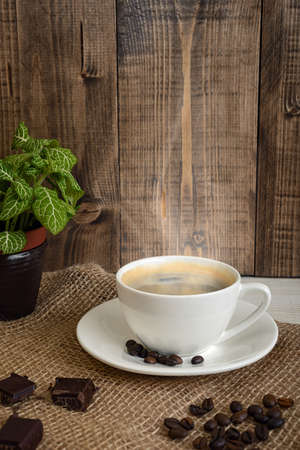 uplifting: Cup of hot fragrant coffee and coffee beans with chocolate on a mesh fabric. Coffee house. Uplifting mood. Coffee break. Relax. Increasing productivity in the mornings. Coffee breakfast.