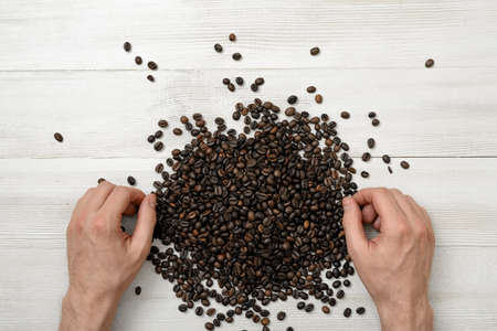 spreaded: Close-up hands of man on a wooden surface with spreaded coffee beans. Grain selection. Top view composition. Workplace coffee maker or sorter. Art composition. Concept. Coffee house. Coffee break.