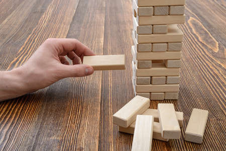 mental activity: Close-up hands of man playing with wooden bricks. Entertainment activity. Education and development. Full concentration. Game of physical and mental skill. Removing blocks from a tower. Keeping balance. Stock Photo