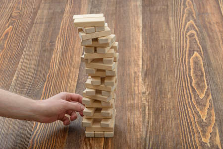 mental activity: Close-up hands of man pulls out wooden bricks. Removing blocks from a tower. Keeping balance. Full concentration. Entertainment activity. Game of physical and mental skill. Close-up photo.