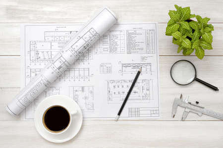 exact: Drawing sketches, magnifier, cup of coffee and houseplant are on wooden surface. Top view compositin. Workplace of architect or constructor. Engineering work. Construction and architecture. Architect drawing. Exact calculation. Office workplace. Increase