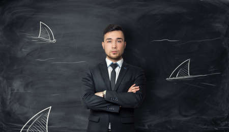 enemies: Businessman stands on background with sketches of shark fins. Symbol of fearlessness, sophisticated cunning, power and danger. Dangerous world of business and finance. Surrounded by enemies.