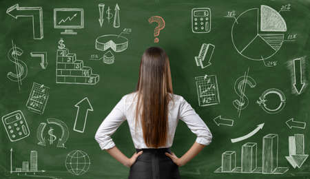 predicament: Back view of businesswoman with question mark over her head on green background with finance graphs. Confusion. Predicament. Financial and business concept. Economic and statistical graphs. Stock Photo