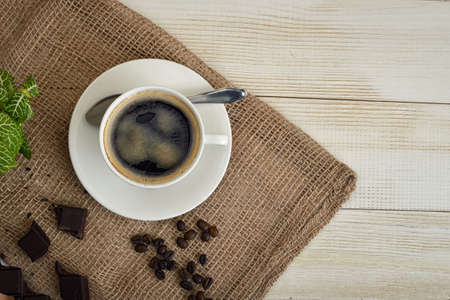 uplifting: Top view of cup of hot fragrant coffee and coffee beans with chocolate on a mesh fabric. Coffee house. Uplifting mood. Coffee break. Relax. Increasing productivity in the mornings. Coffee breakfast. Stock Photo