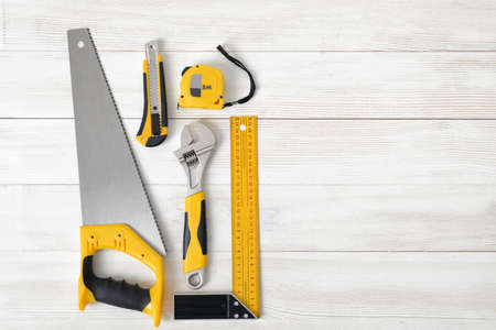 fastener: Building tools including centimeter ruler, wrench and cutter placed in the left side on wooden surface with open space. Top view composition. Hand tool. Tools for carpentry work. Type of fastener. Stock Photo