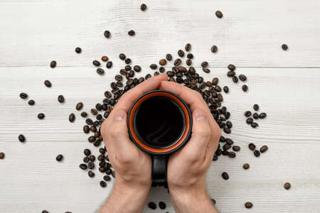uplifting: Close-up hands of man holding a cup of coffee. Top view. Workplace of office man. Coffee house. Uplifting mood. Coffee break. Willingness to work overtime. Increasing productivity in the mornings.