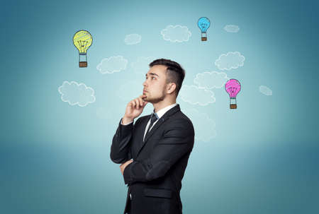 decisionmaking: Thoughtful man on blue background with hand-drawn bulb-parachutes and clouds. Business concept. Good idea is the way to wealth and success. Formation of ideas. Decision-making. Business idea.