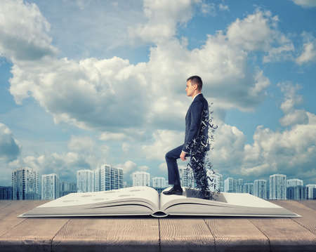 career success: Businessman coming out of the book on cloudy city background. Targeting success and happiness. Success and development. Inspiration. Business idea. Believe in yourself.