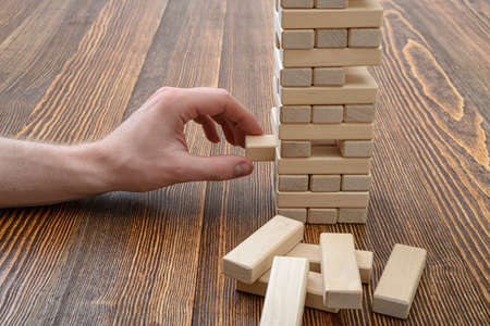 mental activity: Close-up hands of man playing with wooden bricks. Entertainment activity. Education and development. Full concentration. Game of physical and mental skill. Removing blocks from a tower.