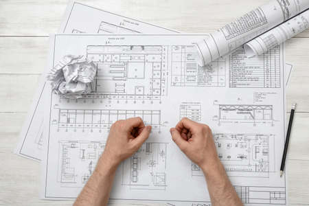 architect drawing: Close-up hands of architect working with a drawing. Workplace of architect. Engineering work. Construction and architecture. Architect drawing. Non-stop work.