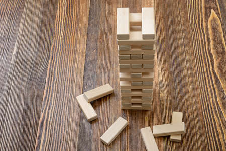 mental activity: The tower of wooden blocks placed on a table.. Removing blocks from a tower. Keeping balance. Full concentration. Entertainment activity. Game of physical and mental skill. Close-up photo. Stock Photo