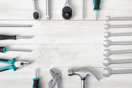herramientas de carpinteria: Vista superior de herramientas de construcción, incluyendo el martillo y destornilladores diferentes tamaños, llaves sobre la superficie de madera con un espacio abierto. Herramientas para el trabajo de carpintería. Tipo de elemento de fijación. Reparar y reparación. Piezas para su reparación. Foto de archivo