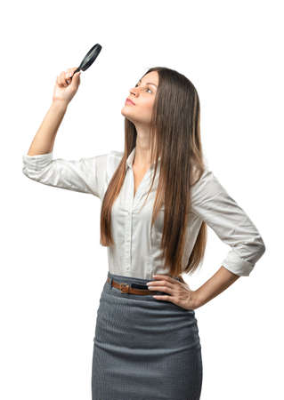 emergence: Cutout businesswoman studies something through a magnifier. Thinking process. The emergence of new ideas. Success and development. Business staff. Office clothes. Dress code. Presentable appearance. Successful lifestyle.