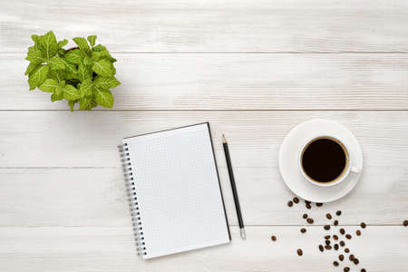 pencil plant: Workplace with cup of coffee, indoor plant, empty notebook and pencil on wooden surface in top view. Office workplace. Vivacity in the mornings. Keeping healthy. Coffee breakfast. Increase working efficiency. Improving mood and productivity. Reducing stre