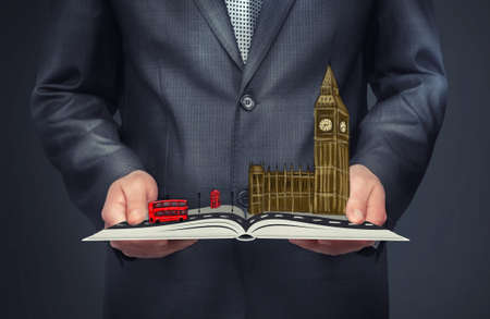 westminster: A businessman holding an open book with a sketch of London on the top of it. Big Ben, Palace of Westminster. Double-decker bus.. City of London. Leading global city in finance and business. Stock Photo