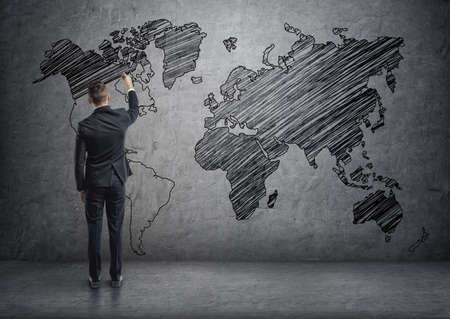 A businessman drawing world map on the concrete wall. Unlimited possibilities. The world is your oyster. Business travel. Politics and diplomacy.