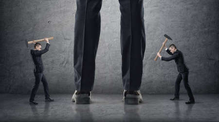 Two businessmen hitting giant legs of another with hammers on a concrete background. Abstract concept. Small business against big. Office confrontation. Problems and troubles.