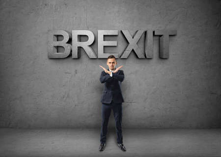 prohibitions: Young businessman making X sign with his arms on the concrete backround with brexit word. Prohibitions and restrictions. Body language. Office clothes. British withdrawal.