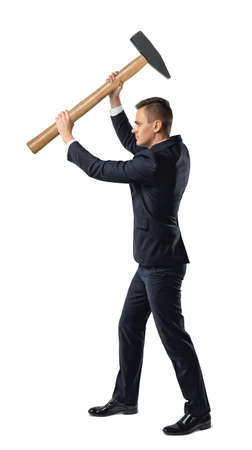 Businessman standing side view to the camera in a suit raising a big mallet above his head in a conceptual image isolated on white Stock Photo