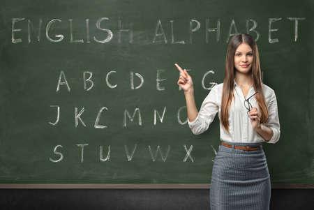 Aantrekkelijke jonge vrouw leraar in een klaslokaal het onderwijzen van de Engels taal met een hand geschreven alfabet op het bord Stockfoto