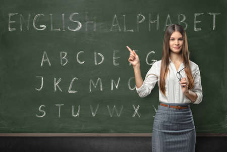 Attractive young woman teacher in a classroom teaching the English language with a hand written alphabet on the chalkboard