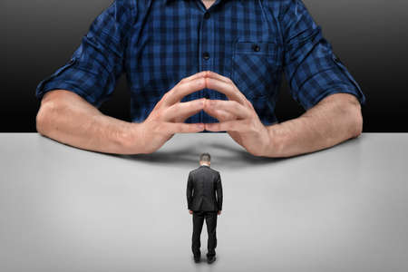bowed head: Businessman with bowed head stands in front of a cropped portrait of a big man sitting with his fingers clasped. Business staff. Boss and employee. Implicit obedience. Guilt and humiliation.