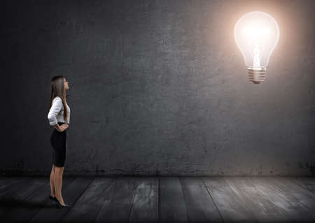 glowing light bulb: Young businesswoman standing and looking at big glowing light bulb in front of her. Stock Photo