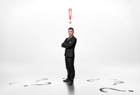 Businessman stands with folded arms with an exclamation mark above him and question marks on the floor isolated on white background. Stock Photo