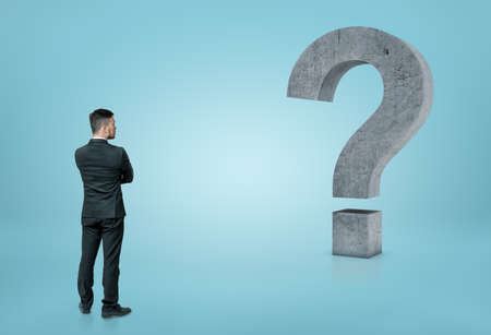 Back view of a businessman looking at big 3D concrete question mark isolated on blue background. Ideas and concepts. Business staff. Solving problems. Confusion and uncertainty.