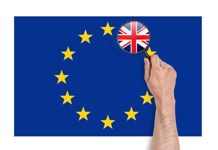 withdrawal: Top view of a mans hand holding a magnifier over EU flag with magnified flag of UK. Brexit. British withdrawal. Significant decision. Substantial choice. Stock Photo