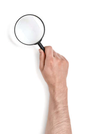 Hand of man holding the magnifying glass isolated on white background. Top view.