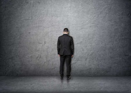 bowed head: Back view of a businessman with bowed head standing in front of a concrete wall. Problems and doubts. Business staff. Ideas and concepts.