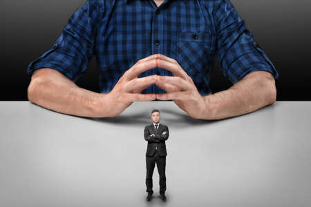 Businessman with folded arms stands in front of a cropped portrait of a big man sitting with his fingers clasped. Stock Photo
