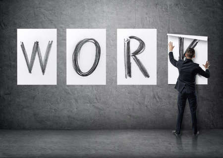 concrete form: Businessman putting up posters with letters on a concrete wall that form a work word. Stock Photo