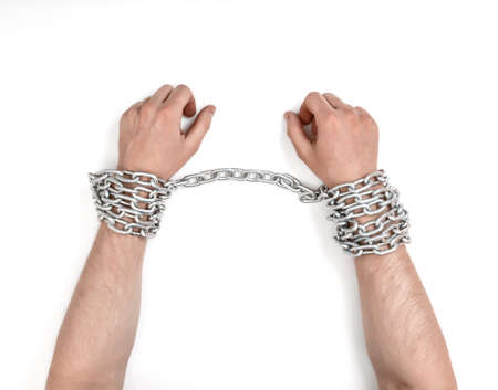 Close up view of chained mans hands.