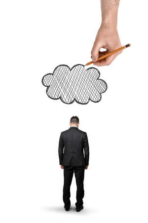 unfortunate: Back view of a businessman with bowed head standing and a big hand above that draws a cloud isolated on white background.