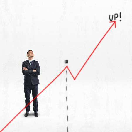 Businessman stands with folded arms looking upwards behind big rising diagram isolated on white background.