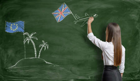 Businesswoman drawing a plane with british flag that flies away from an island with EU flag on blackboard.