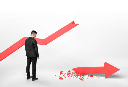 broken back: Back view of a businessman looking at broken arrow that fall off the graph.