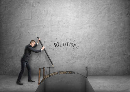 Businessman drawing a bridge over a gap with word solution above it.