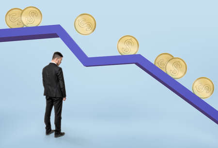 bowed head: Businessman with his head bowed standing under falling graph with golden coins rolling down.