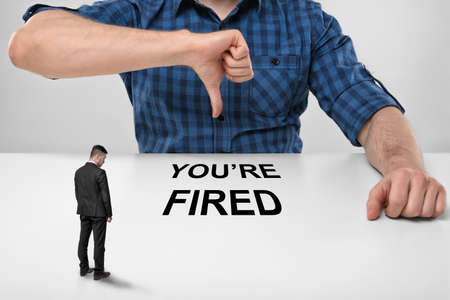 bowed head: Small businessman with bowed head standing in front of cropped portrait of big boss showing thumb down with words youre fired under his finger. Stock Photo