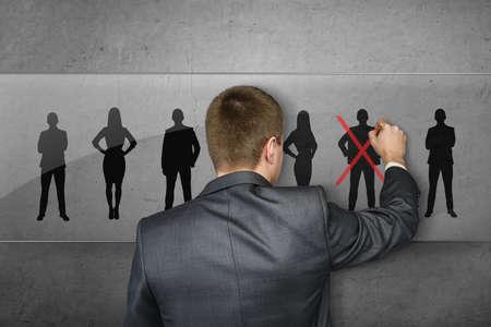 Vista posterior de un hombre de negocios delante de una fila de siluetas de dibujo cruz roja sobre una de las personas.
