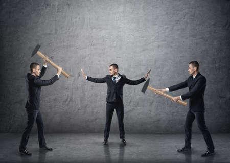Homme d'affaires avec des mains surélevées séparant deux hommes d'affaires de combat avec des marteaux. Banque d'images - 62273738