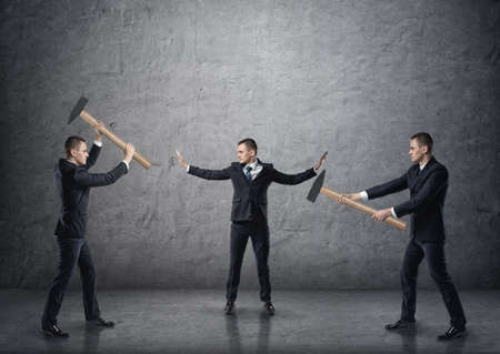 Businessman with raised hands separating two fighting businessmen with hammers.