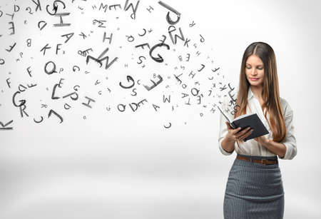 gaining: Young businesswoman with a notebook with letters flying out of it. Gaining knowledge. Intelligent and smart. Learning and teaching.